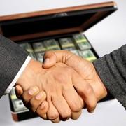Handschlag vor Geldkoffer